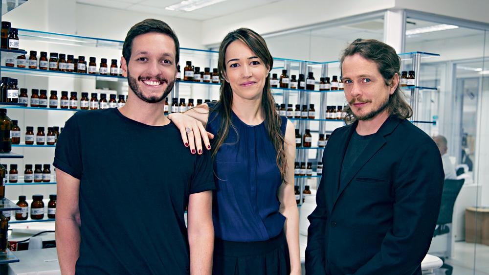 Isaac, Fany e Fábio sorrindo para a foto entre prateleiras de frascos de fragrâncias
