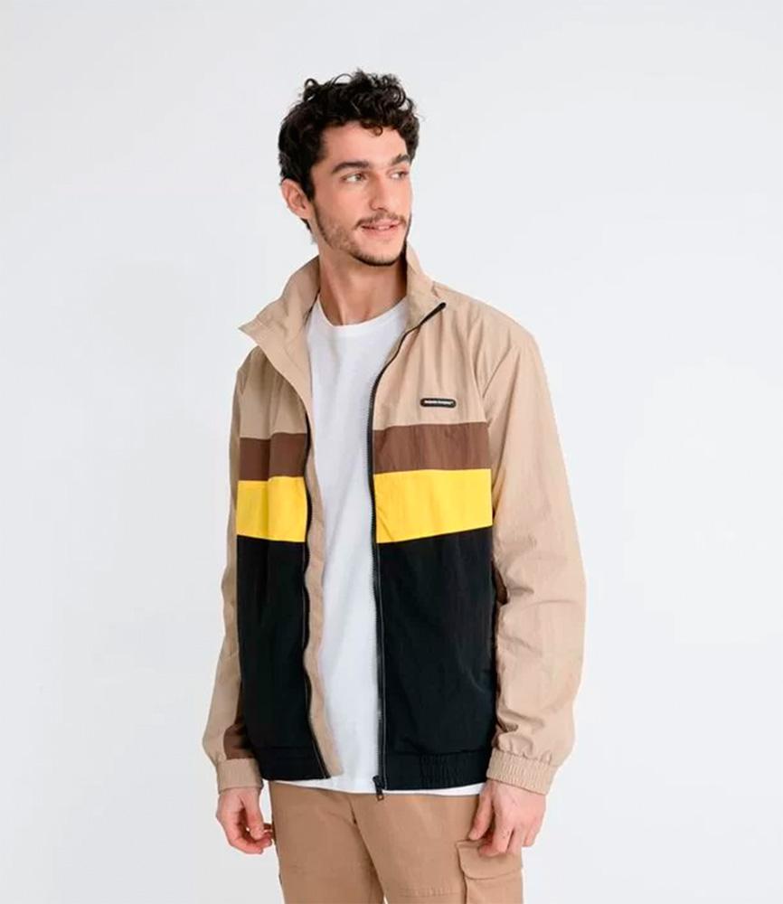 Homem veste camisa branca e jaqueta bege com detalhes em amarelo, preto e marrom. Ele olha para o lado
