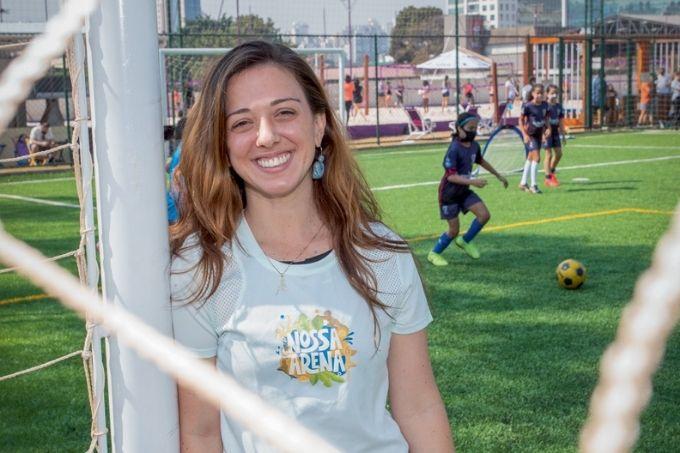 foto de julia vergueiro de trás de barbante do gol. ela está encostada em trave de gol e com camisa do nossa arena. ao fundo, mulheres estão jogando futebol utilizando máscaras