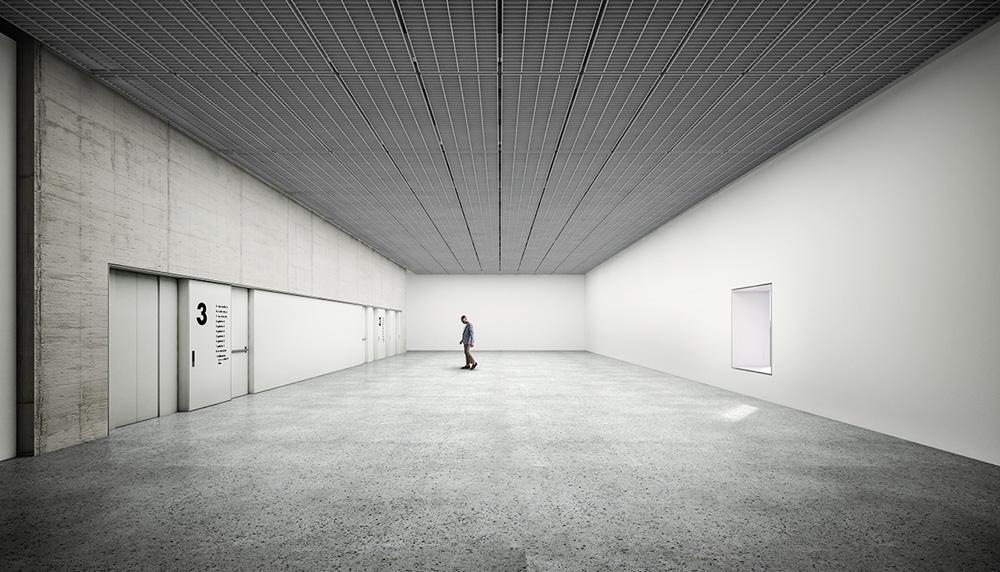 A imagem mostra um sala grande e vazia, com apenas uma pessoa nela, dando noção do tamanho do ambiente.