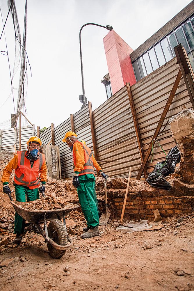 A imagem mostra um canteiro de obras, com dois funcionários trabalhando em meio a terra. Ao fundo, é possível ver uma parte do Masp acima de um tapume do canteiro.