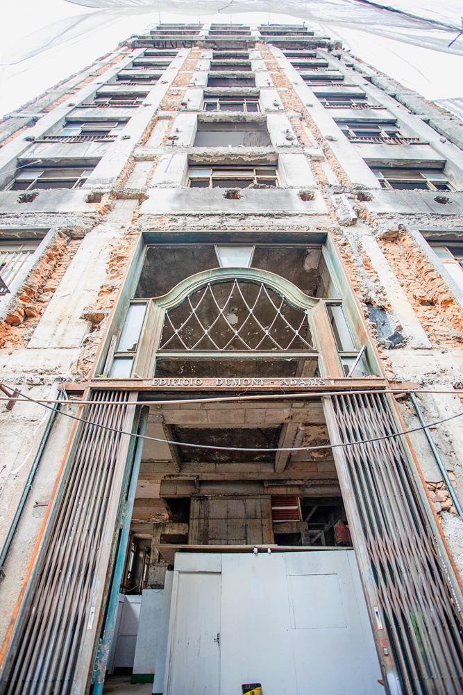 A imagem mostra a fachada, evidentemente desgastada, do Dumont-Adams, em uma visão da calçada olhando para cima.