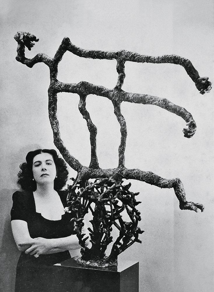 A imagem mostra Maria Martins, de braços cruzados, ao lado de uma escultura surrealista feita por ela. São quatro galhos espinhentos, fazendo a forma de uma bola. Em cima deles, há outros galhos mais grossos e sem espinhos e sem formato definido.