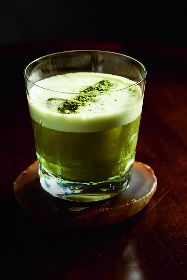 Drinque de cor verde com espuma branca em copo baixo de vidro sobre porta-copos.