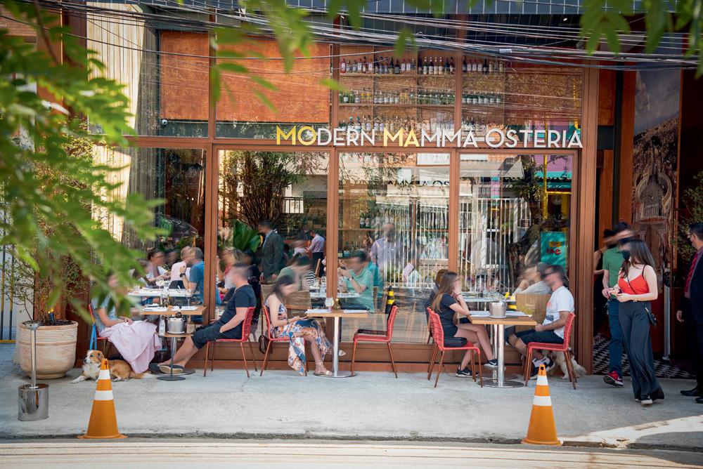 Fachada envidraçada do restaurante Moma Modern Mamma Osteria em Pinheiros com pessoas sentadas em mesas na calçada.