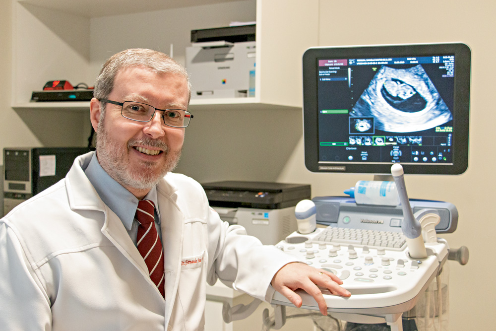 A imagem mostra Fernando, em um consultório médico, vestido com um jaleco branco. Ele está sentado, sorrindo para a foto e ao fundo há uma imagem de um ultrassom.