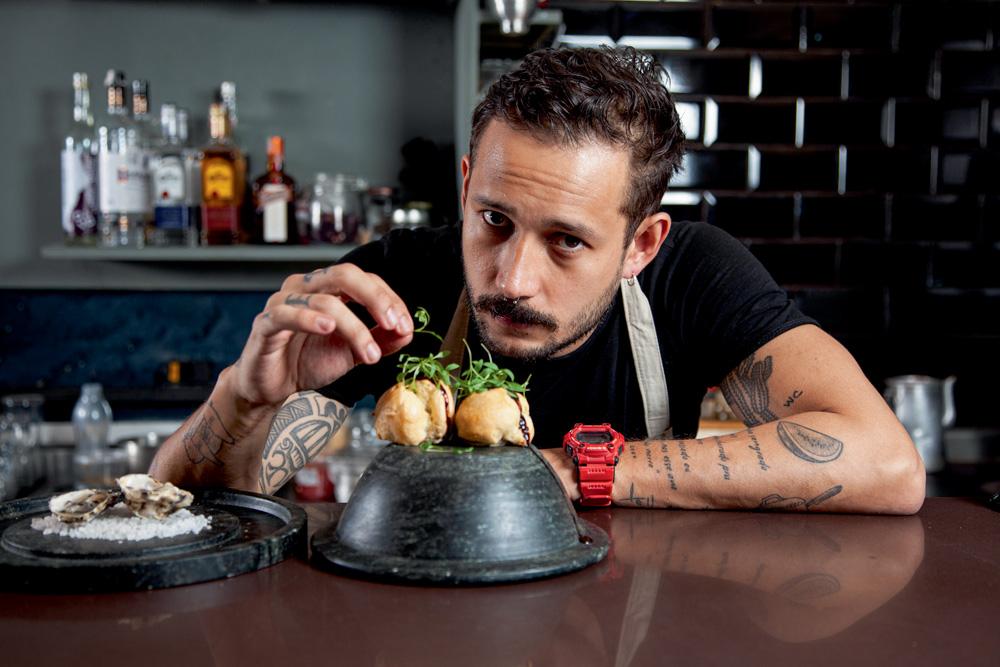 Chef Giovanni Renê posa finalizando prato a sua frente na cozinha do Davo.