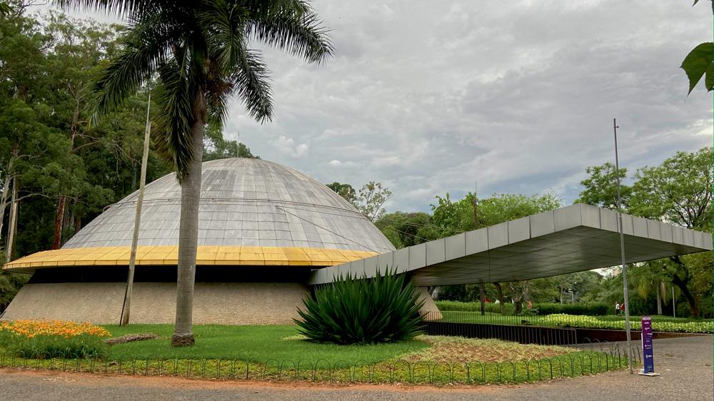 A imagem mostra uma foto do Planetário do Ibirapuera. É um domo, cinza, com uma entrada coberta por um telhado cinza.