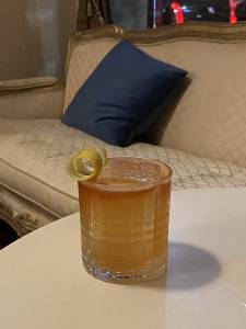 Em um copo redondo sobre uma mesa, é servido drinque de cor alaranjada decorado com casca de laranja