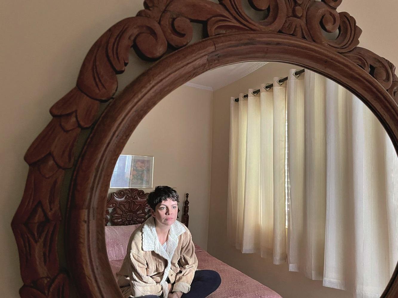 Mulher está sentada em uma cama e dá para vê-la pelo reflexo de um espelho