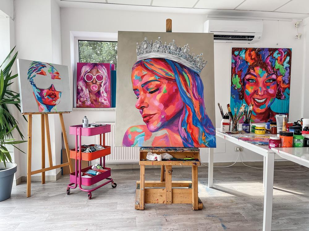 Obra de Ramona Pintea aparece erguida em um ateliê. O quadro exibe o rosto de Natalia Martins em versão colorida (rosa, azul e roxo) com uma coroa na cabeça).