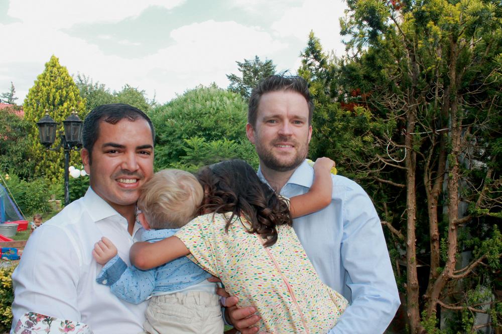 A imagem mostra Rodrigo e Hohmann segurando seus dois filhos, que estão de costas para a câmera. O casal de pais está sorrindo para foto enquanto seus filhos os abraçam na altura dos ombros.