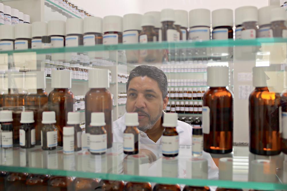 Samuel Moraes fotografado por detrás de prateleira translúcida de frascos de fragrâncias analisando-os
