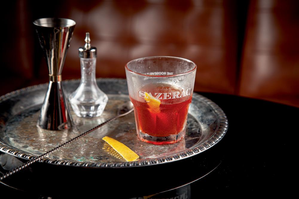 Drinque vermelho em copo de vidro sobre bandeja de preta em cima de mesa prata.