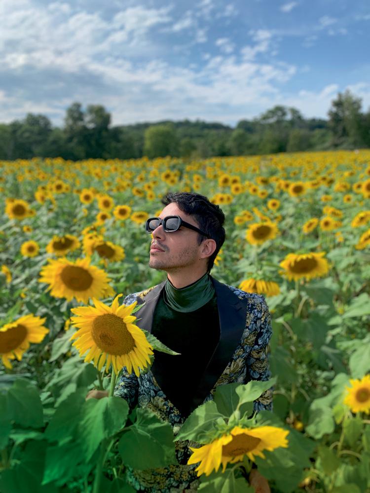 Tiago Motta em meio a campo de girassois com parte superior do tronco e cabeça visíveis, olhando para o céu de camisa preta e óculos escuros