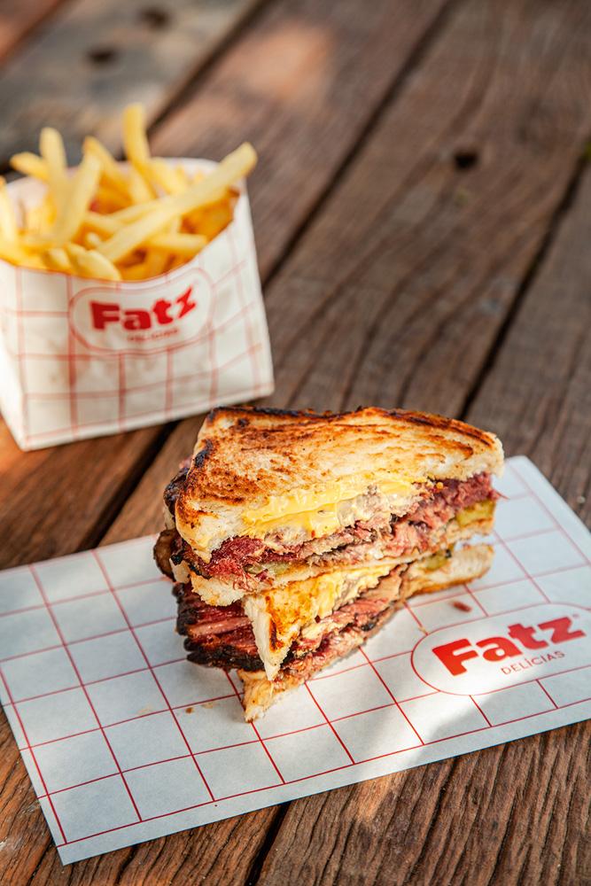 Dois pedaços, um sobre o outro, de sanduíches em pão de fôrma recheados de queijo cremoso e pastrami em cima de papel listrado branco e vermelho sobre mesa de madeira. Ao fundo batatas fritas em saquinho branco.