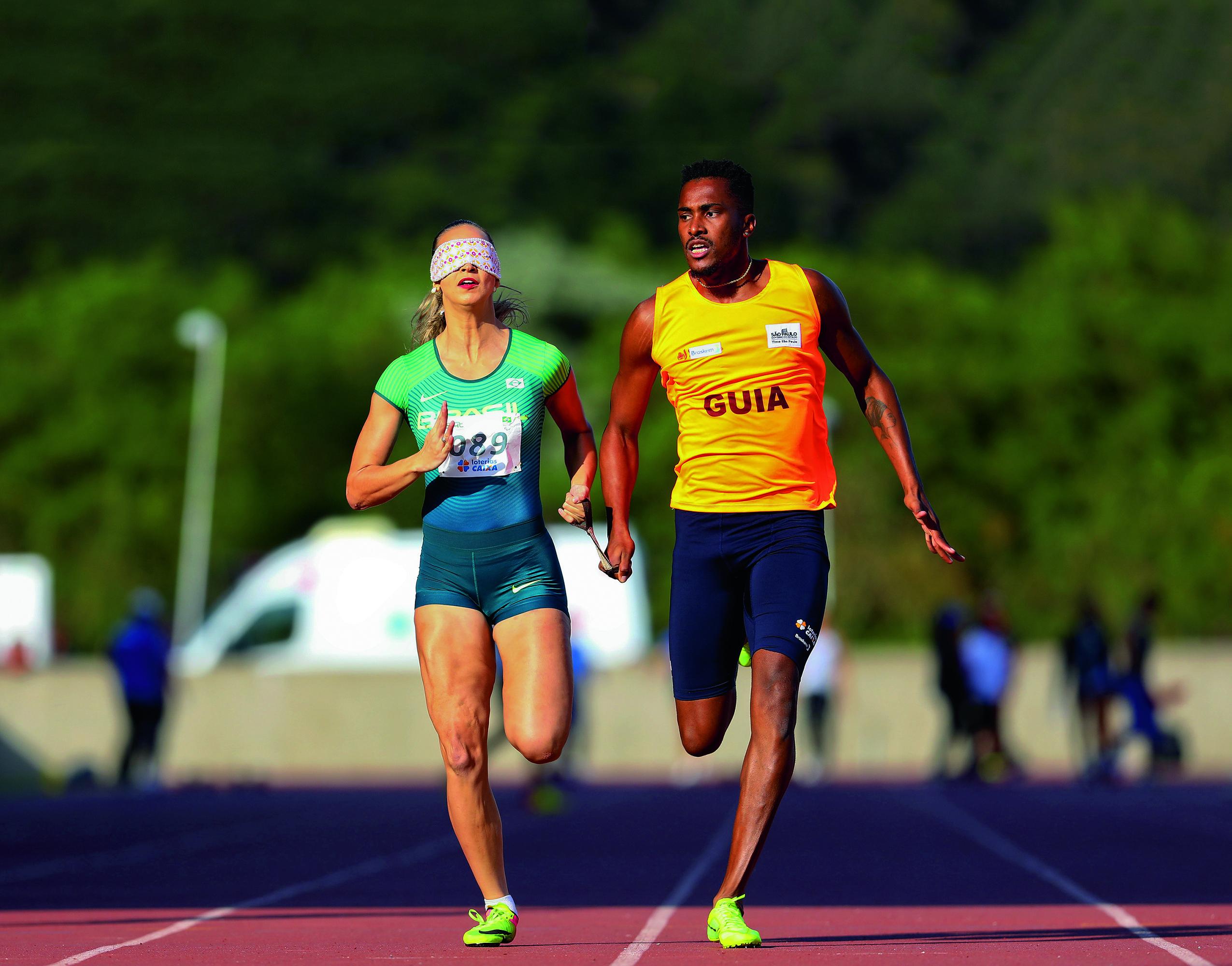 Uma atleta com uma venda no rosto corre na pista com seu guia