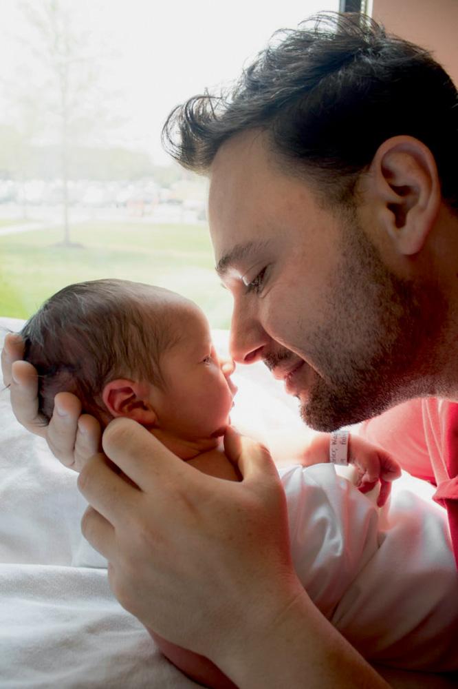 A imagem mostra Wagner segurando o recém nascido Arthur com as duas mãos. Eles tocam os narizes, olho a olho, e o pai está sorrindo.