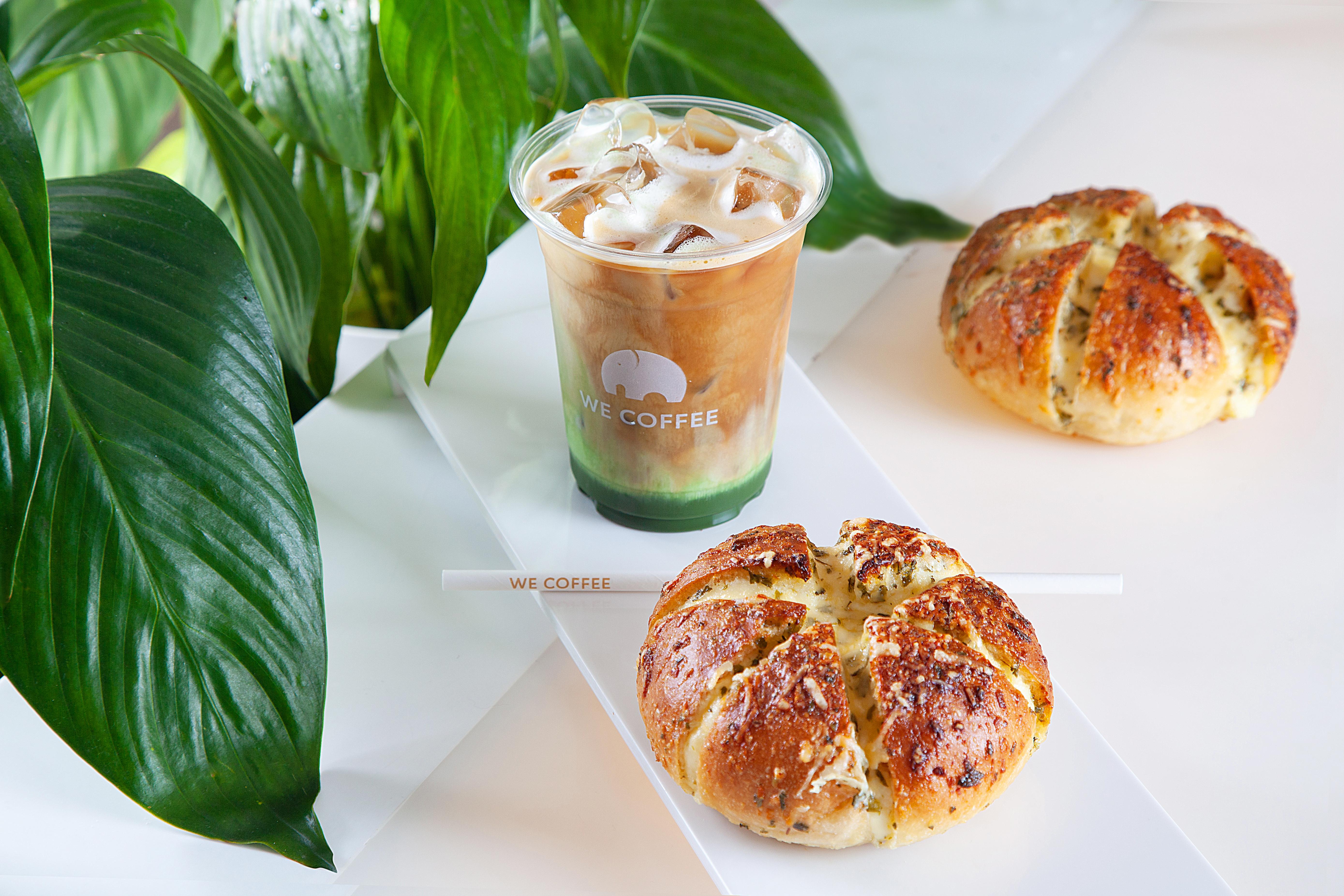 Pão de alho arredondado sobre bancada branca e café com doce de leite e matchá num copo de plástico transparente atrás.