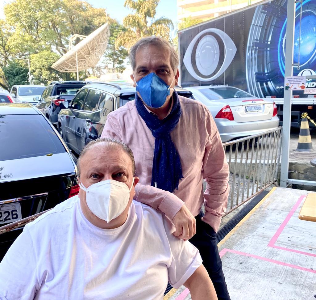 Erick Jaqcuin sentado ao lado de Arnaldo Lorençato na frente dos estúdios da Band. Ambos de máscara.
