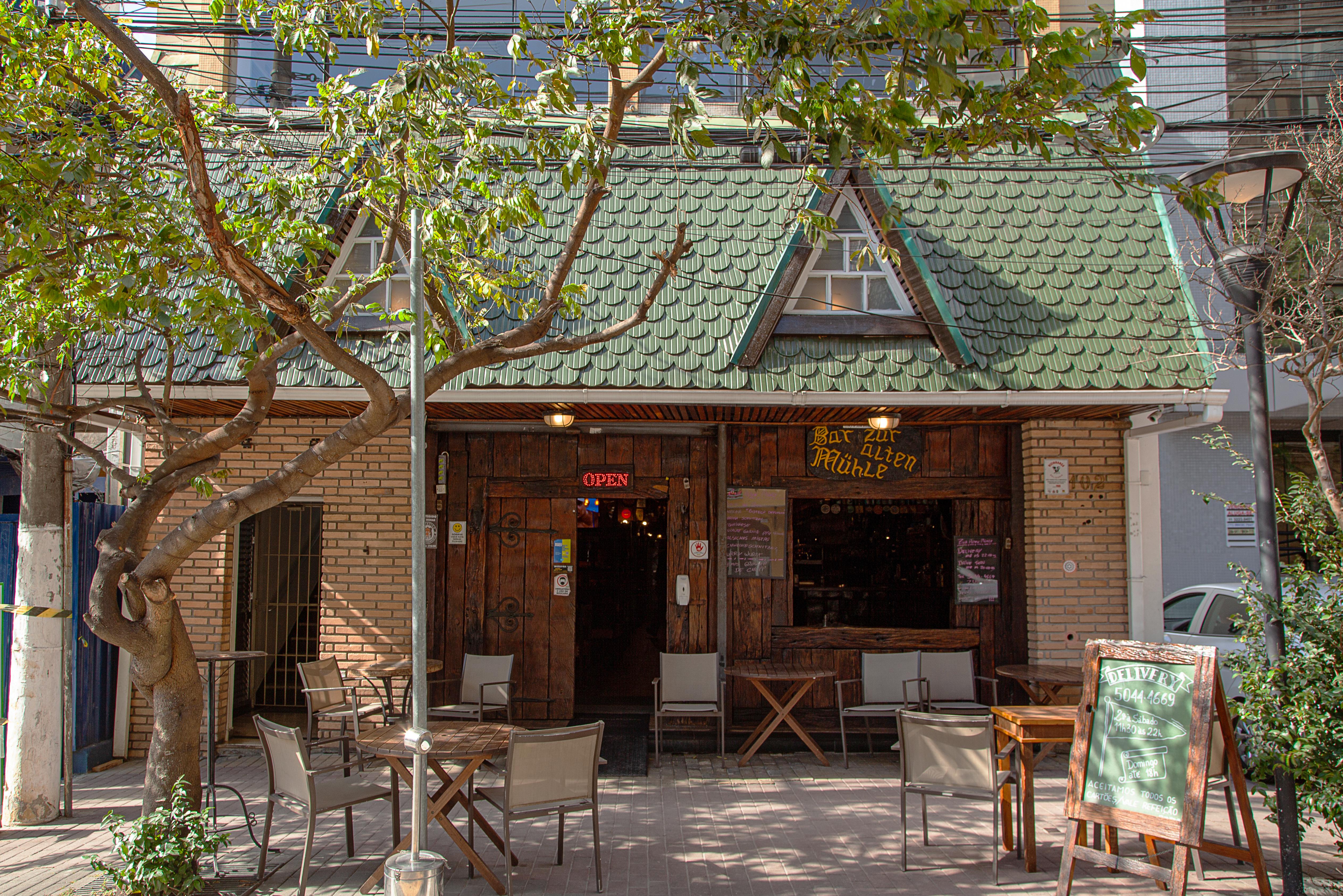 Fachada do bar Zur Alten Mühle, com telhadinho verde e parede de tijolos.