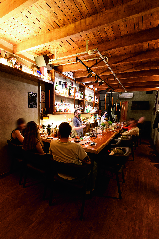 Balcão do The Punch Bar à esquerda com clientes sentados em banquetas.