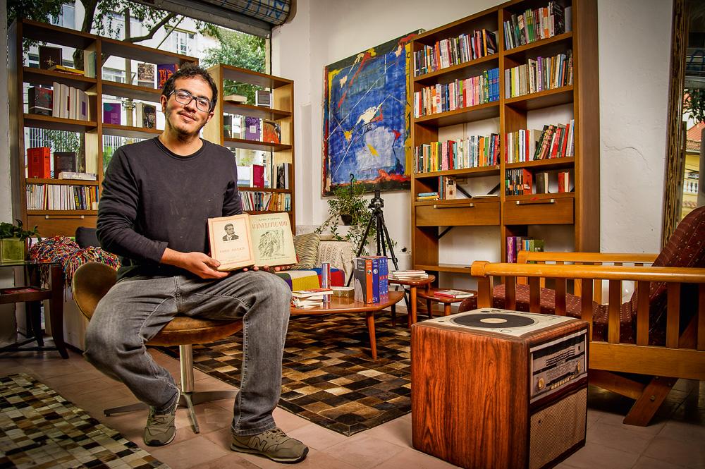 bruno eliezer sentado em sua livraria, ponta de lança. ele está segurando livro aberto