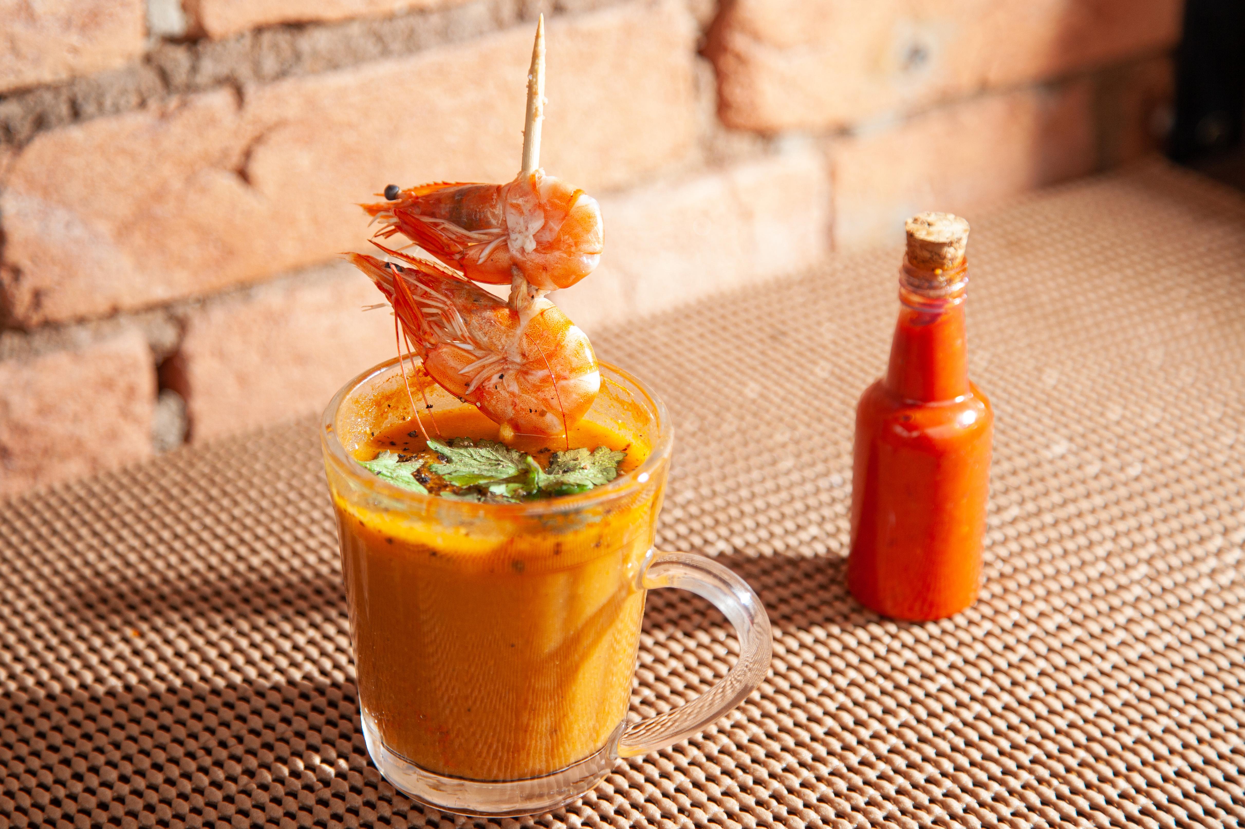 Caldo de camarão servido em pequena xícara de vidro transparente com espeto de camarões por cima ao lado de vidrinho de pimenta.