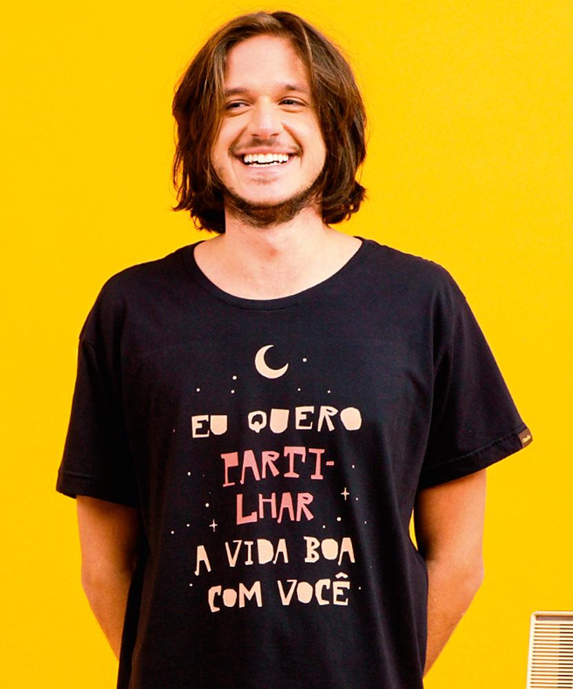 Um homem sorri em um fundo amarelo vestindo uma camiseta preta com a frase
