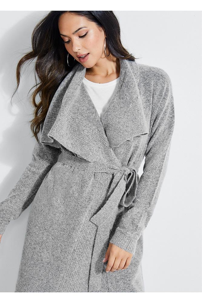 Mulher olha para baixo posando com um casaco estilo sobretudo cinza