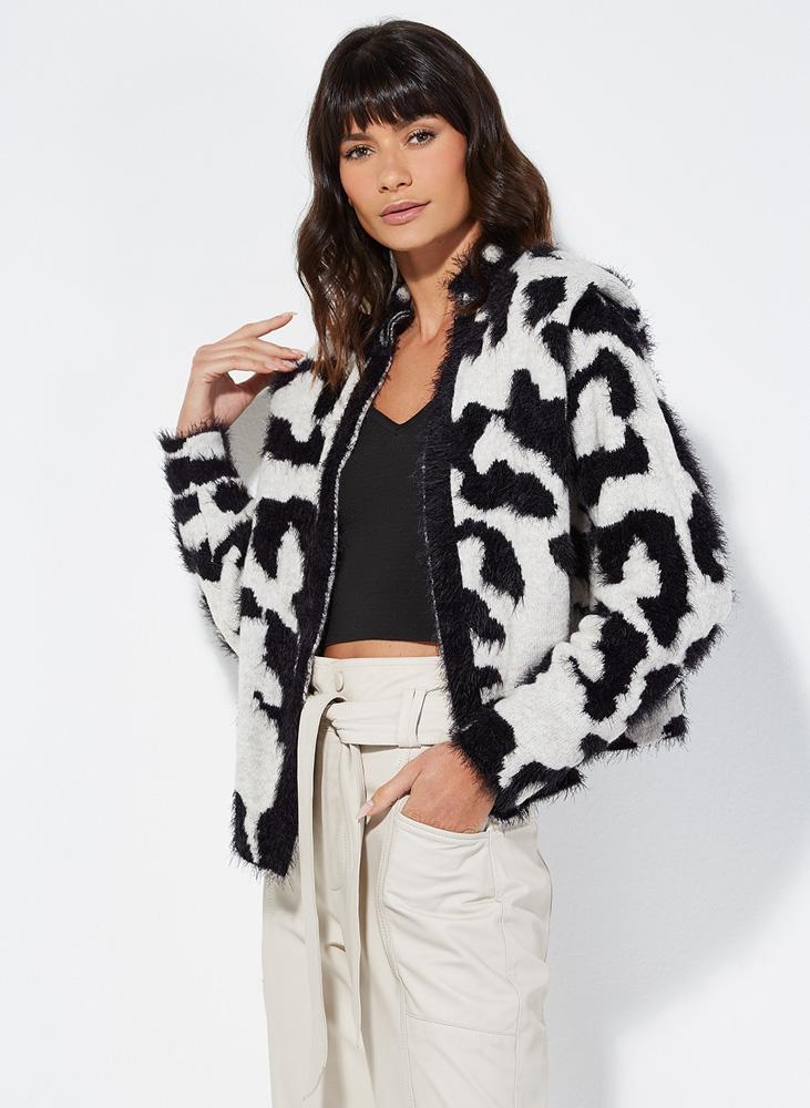 Mulher posa olhando para a câmera com jaqueta estampada em preto e branco com formas redondas