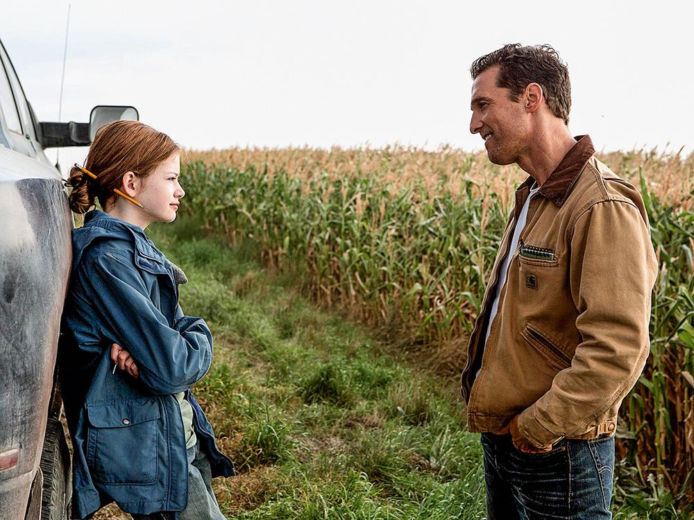 A imagem mostra cena do filme interestelar. É uma pai e uma filha, ela está encontrada na porta de um carro com as costas, olhando para seu pai, que por sua vez está com as mãos no bolso. Ao fundo, há uma enorme plantação.