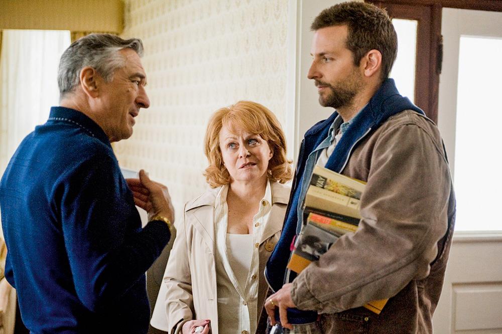A imagem mostra três atores de O Lado Bom da Vida. Um senhor discute com um jovem, que está cheio de livros na mão. Uma senhora mais ao fundo olha com desconfiança para o senhor que está falando.