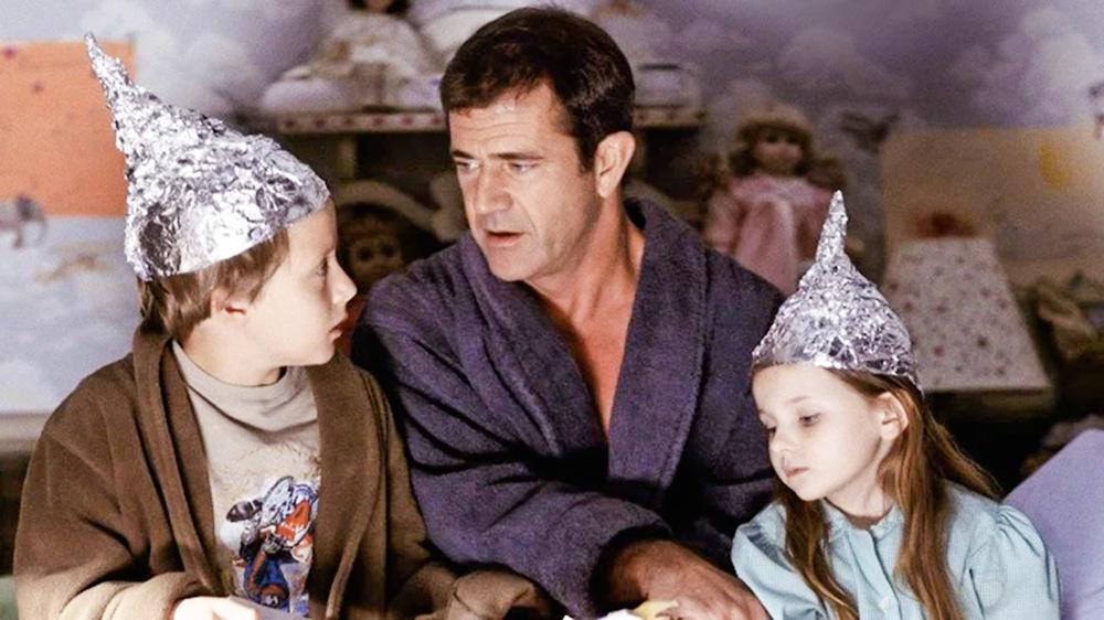 A imagem mostra o pastor, de roupão, segurando na mão de duas crianças, falando algo para as duas que estão prestando atenção.