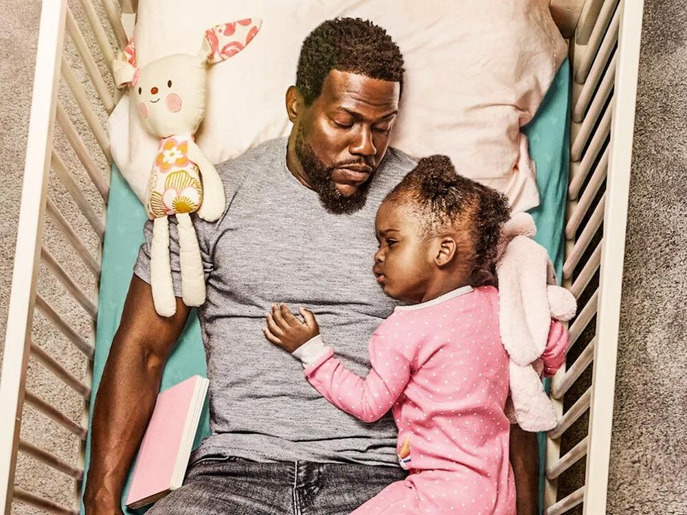 A imagem mostra Kevin deitado em um berço com um bebê apoiado em seu peitoral.