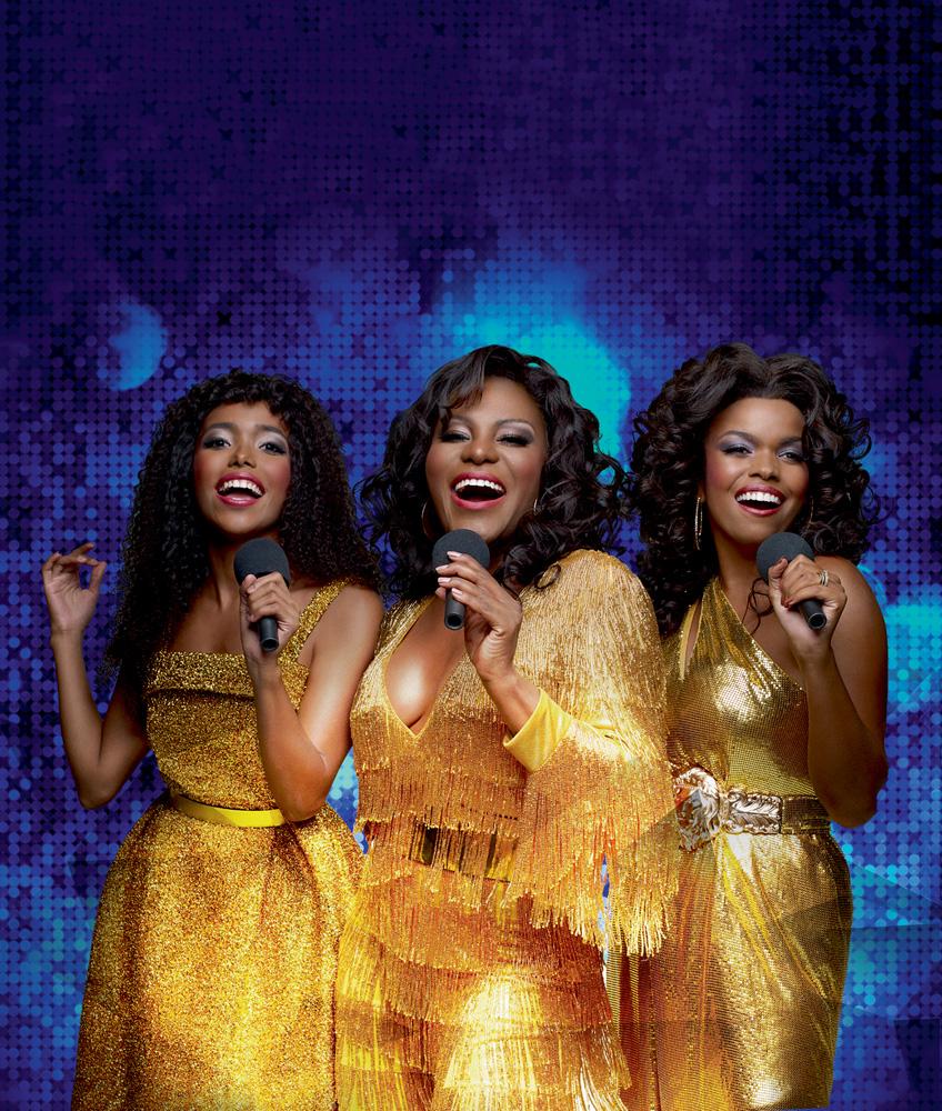 A imagem mostra as três atrizes mencionadas na legenda, todas vestidas de dourado e cantando com microfone na mão em um fundo azul brilhoso.