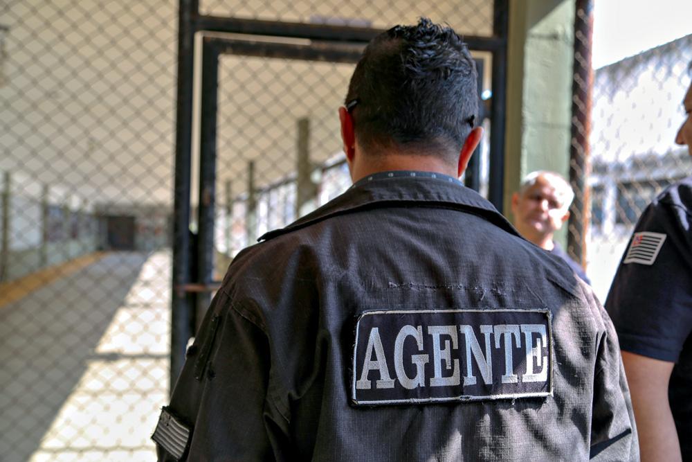 A imagem mostra um homem virada de costas para foto. Em sua jaqueta está escrito AGENTE.