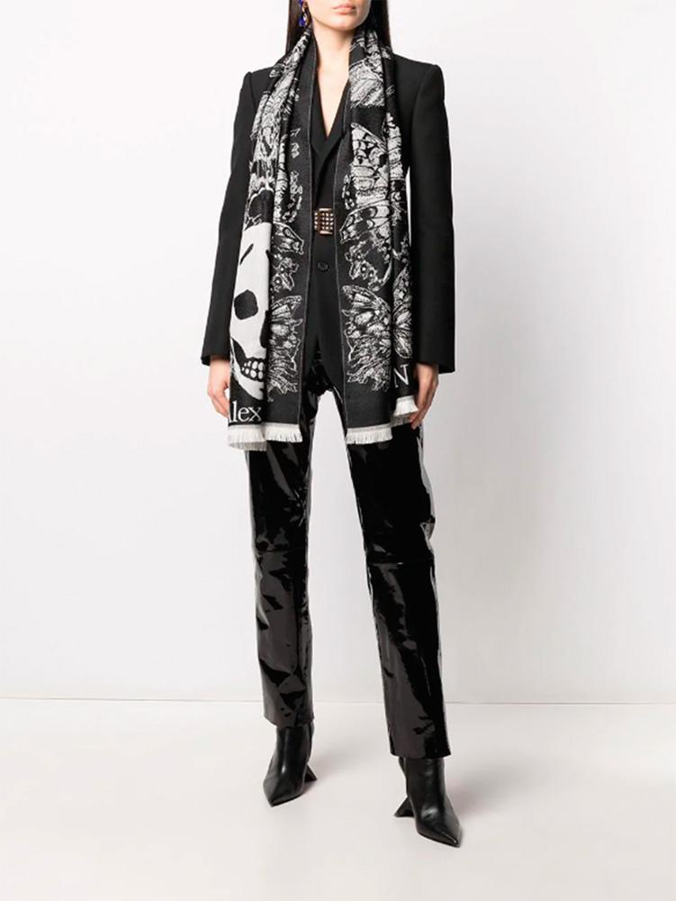 Imagem mostra só corpo de mulher vestindo preto e um echarpe preto e branco com estampa de caveiras