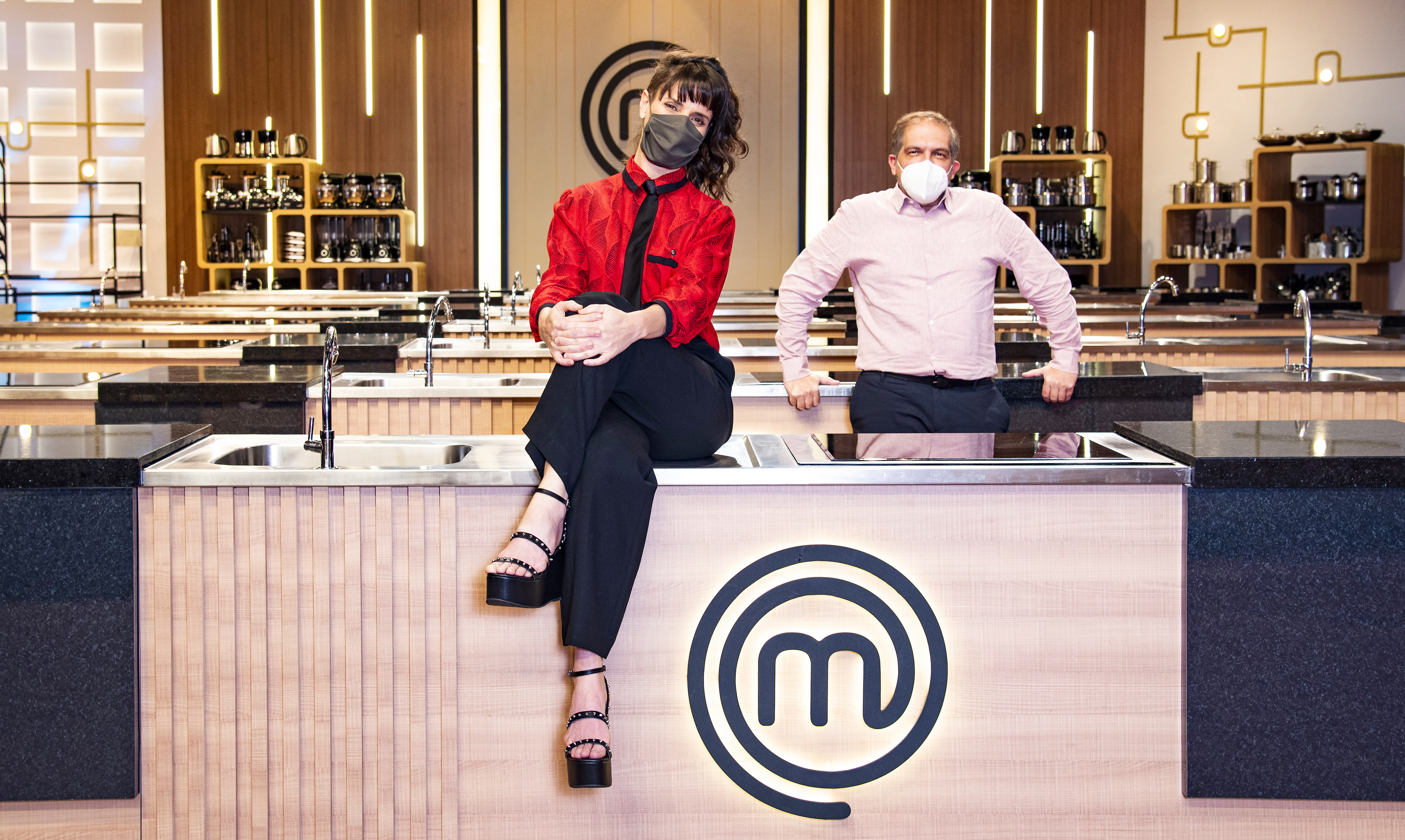 A chef Helena Rizzo sentada na bancada do MasterChef e Arnaldo Lorençato encostado na bancada logo atrás, à direita. Ambos de máscara.