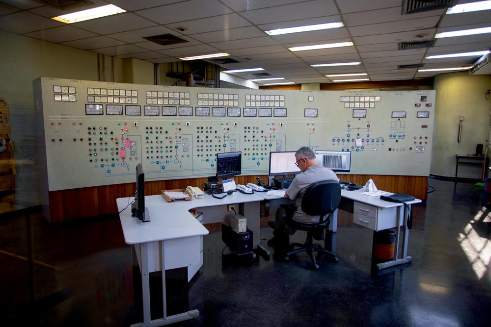 sala de controle da usina de traição, com um painel suspenso com muitos botões e telas. à frente do painel, tem um técnico em sua mesa