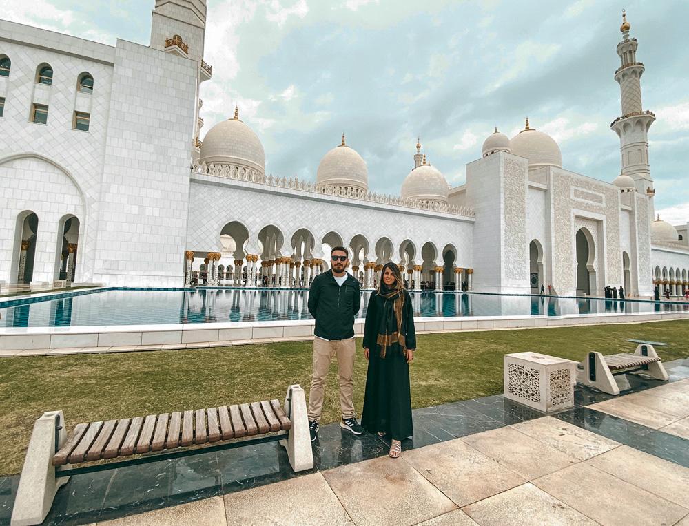 tati e gabriel posando para a foto com mesquita ao fundo, em abu dhabi
