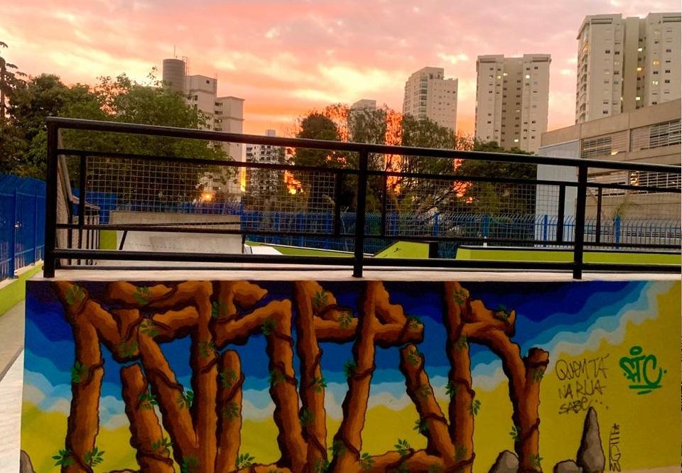 Foto mostra pedaço de uma pista de skate. Em uma parede, há grafite e o céu tem um por do sol alaranjado
