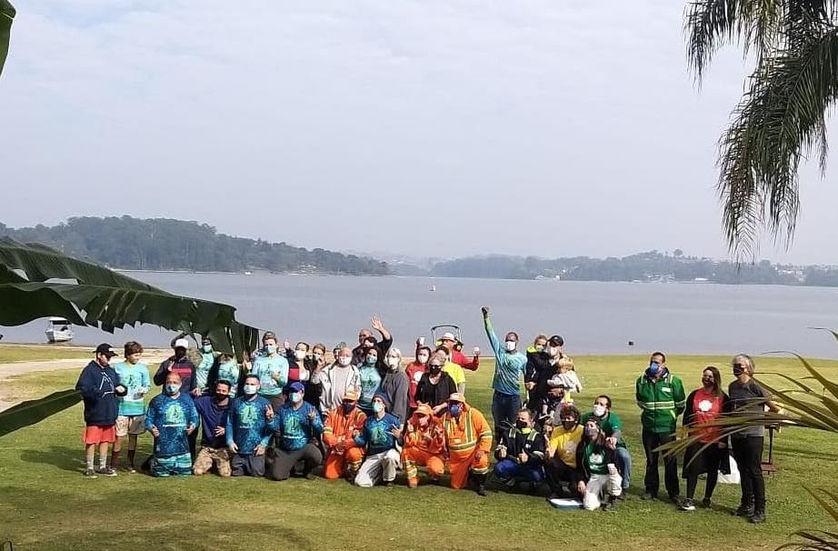 Um grupo de pessoas de várias idades posa em frente a Represa de Guarapiranga; dia está nublado