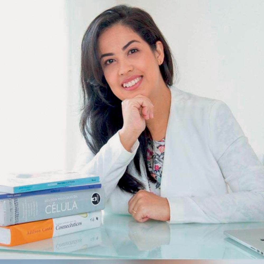 lilian sanpei sentada com cotovelo direito apoiado na mesa e com cabeça sendo sustentada pela mão direita. ela está sorrindo para a foto