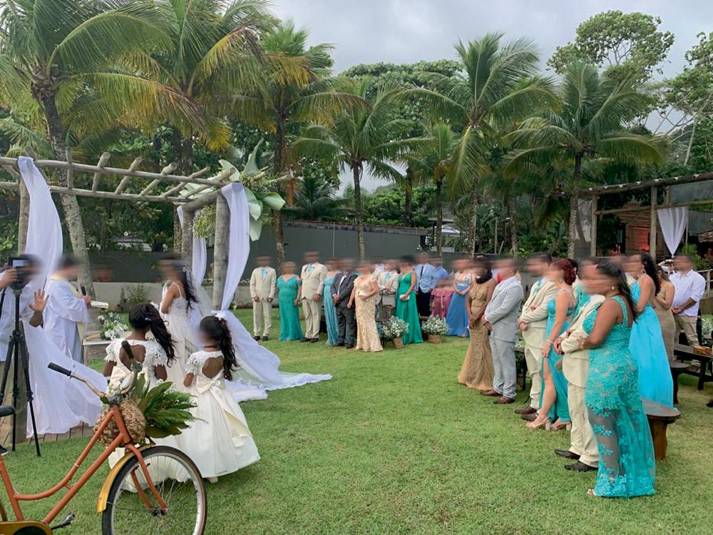 Foto mostra uma cerimônia de casamento em um gramado na praia. Convidados observam o altar