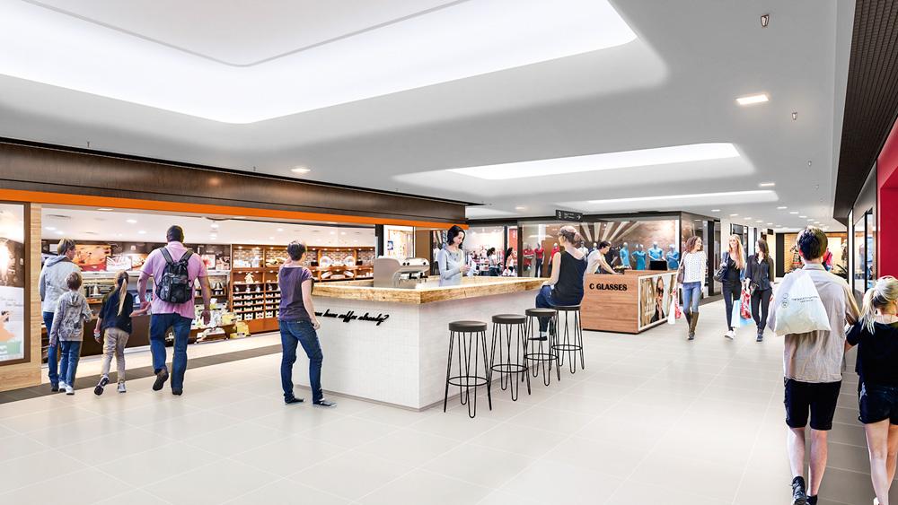 Vista na diagonal de um shopping tem um balcão de uma lanchonete no meio do corredor, pessoas em volta e lojas aos lados