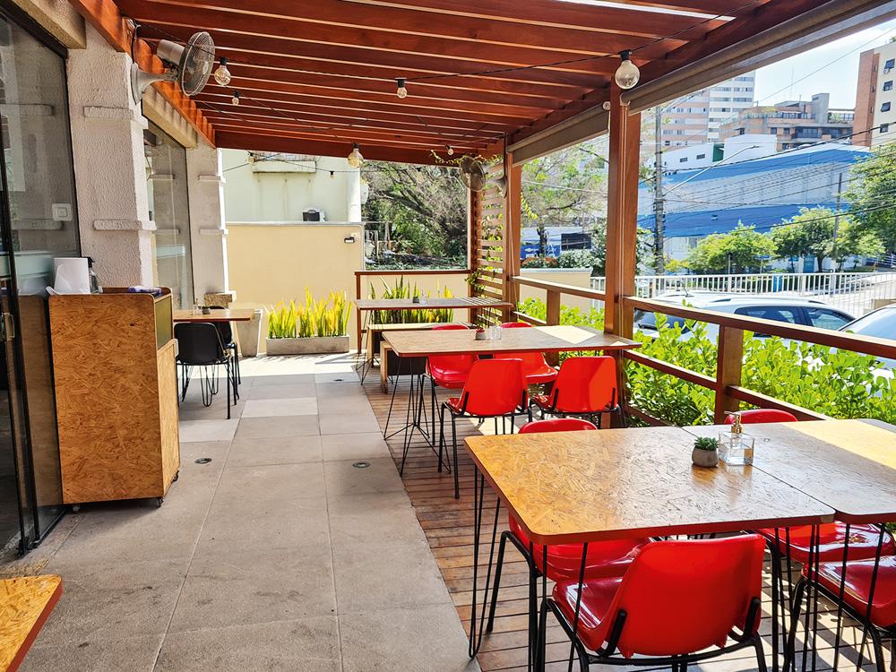 Em uma varanda com pequenas lâmpadas penduradas no teto vazado, quatro mesas estão espalhadas pelo ambiente com cadeiras vermelhas.