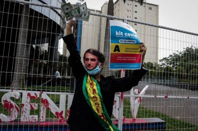 A imagem mostra uma pessoa com máscara de Jair Bolsonaro e faixa presidencial; em uma das mãos ela carrega um cartaz que simula a caixa de um medicamente que fez parte do chamado kit covid e na outra papeis que simbolizam dolares