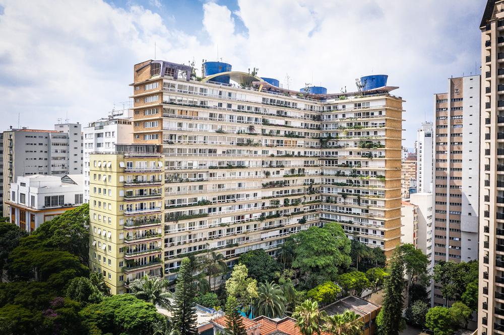 Foto de longe do Edifício Bretagne. Em L, com muitos apartamentos e plantas nas janelas. Dá para ver o entorno da cidade ao redor do prédio