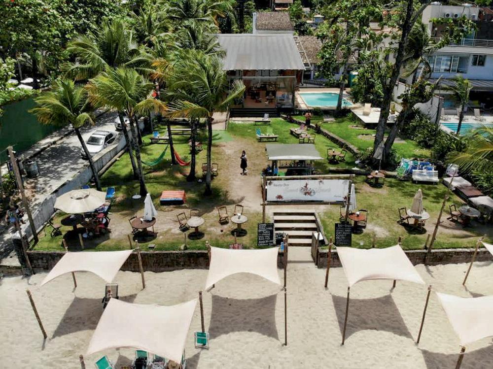 Foto aérea mostra uma área de um bar restaurante à beira-mar. Tem quiosques, piscina e um grande gramado